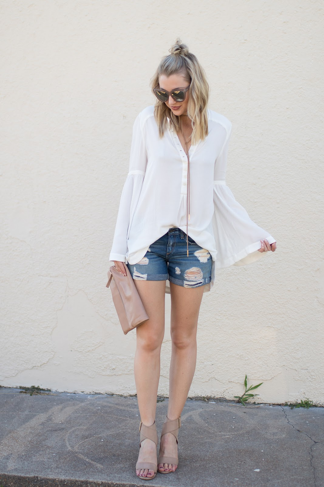 White bell sleeve top with distressed denim shorts