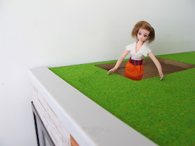 A doll looking through the hole at the top of the stairs to the roof garden of the modern Lori Loft to Love dolls' house.