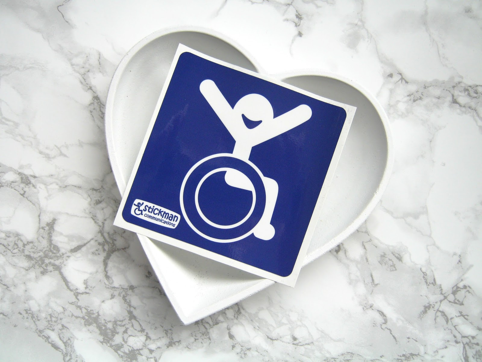 Marble background with a white heart shaped dish on, a blue sticker with a wheelchair symbol rests on the dish