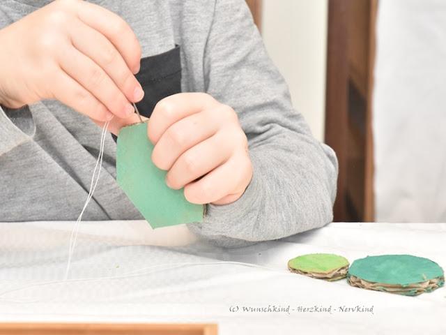 Basteln mit Kindern. Eine Bastelidee für den Frühling. Ein selbstgebasteltes Windspiel. Fördert die Augen-Hand-Koordination, Motorik und die Geduld und beinhaltet ein Upcycling von Karton.
