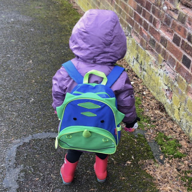 Back view of a toddler wearing the Skip Hop Zoo Dinosaur backpack, a purple coat and pink wellies