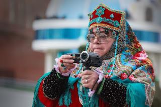 бабушка в национальном костюме с видеокамерой