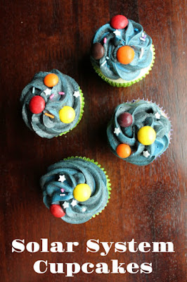 cupcakes with dark frosting and colored candy planets with star sprinkles