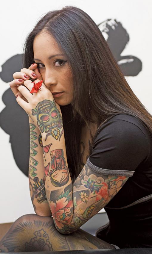 preciosa mujer asiatica, esta sentad con las mnos entrelazadas, nos mira, lleva tatuajes en los brazos, tatuajes de colores vivos