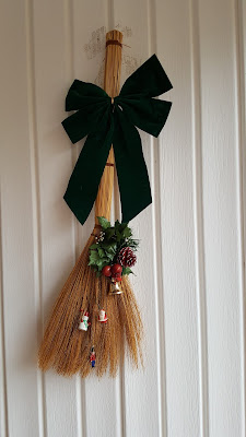broom decorated for Xmas with bows and bells