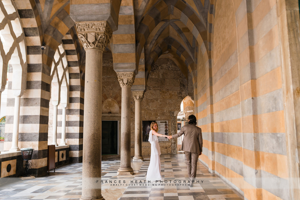Bride and groom walking in the entrance of Amalfi church