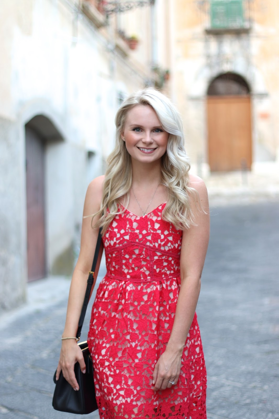 a women walks through tiny streets of old italy with loose blonde curls and red lace dress