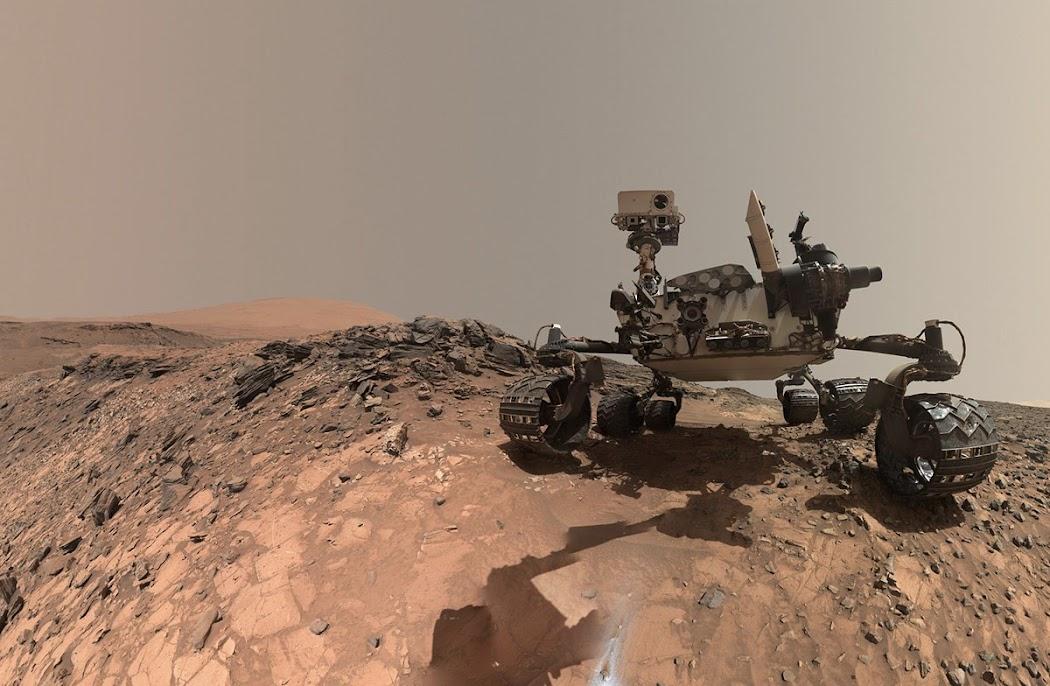 """Curiosity nghỉ chân tại một địa điểm mà tiếp sau đó nó sẽ khoan xuống mục tiêu thăm dò là một hòn đá được gọi là """"Buckskin"""" ở chân núi Sharp. Hình ảnh selfie góc rộng này được chụp vào ngày 5 tháng 8 năm 2015, nhằm sol 1065 và được công bố ở Trái Đất vào ngày 19 tháng 8 cùng năm. Hình ảnh này được ghép lại từ các hình ảnh đơn được chụp bởi thiết bị Mars Hand Lens Imager (MAHLI). Hình ảnh: JPL-Caltech/MSSS/NASA."""