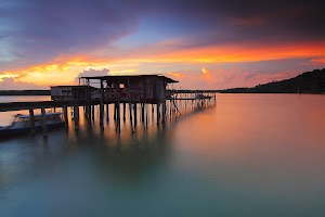 Wooden Cabin On Water And Sunset