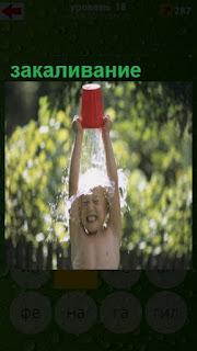 ребенок выливает на себя ведерко воды летом, закаливая свой организм