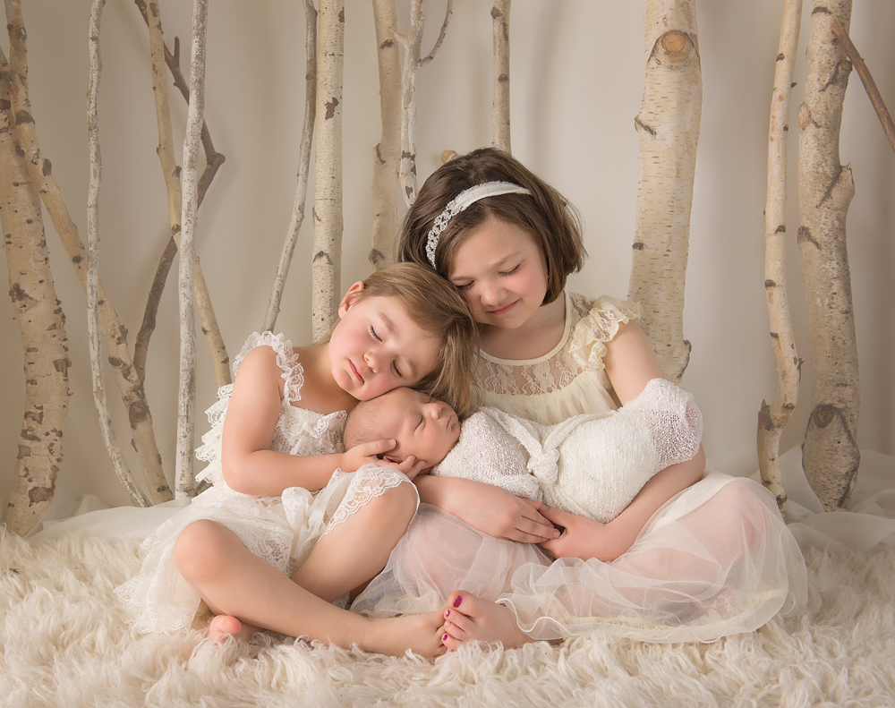 beautiful newborn photo of siblings | two sisters and new baby brother in cream dresses