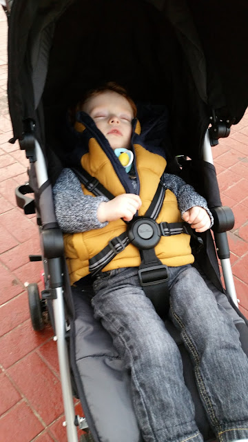 Little boy lying down and sleeping in a pushchair