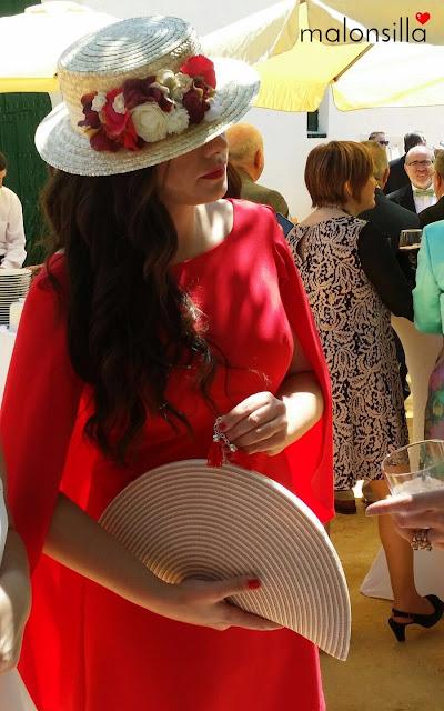 Invitada boda de perfil con canotier, vestido rojo y bolso abanico, con pelo suelto