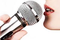 Elindeki kapalı bir mikrofona şarkı söyleyerek pleybek ya da playback yapan bayan sanatçı