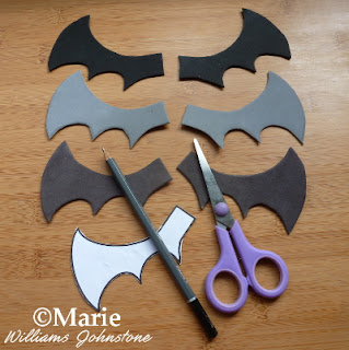 Black and gray wings cut out with scissors, pencil and template