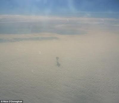 Una extraordinaria fotografía capturada por un pasajero de avión a 30.000 pies muestra lo que parece un robot enorme caminando por las nubes