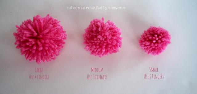 three sizes of handmade pom poms