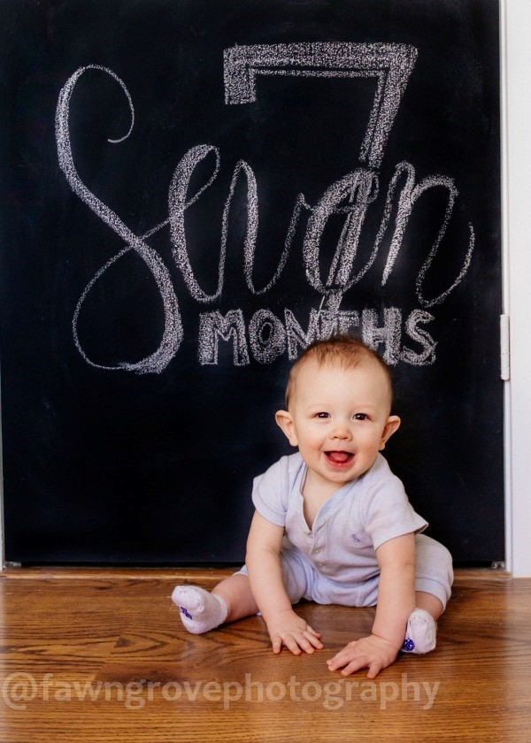 Baby boy sits in front of chalkboard for photo.