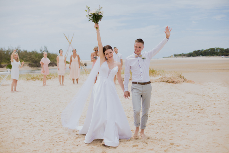 bride and groom with arms in air walking down aisle