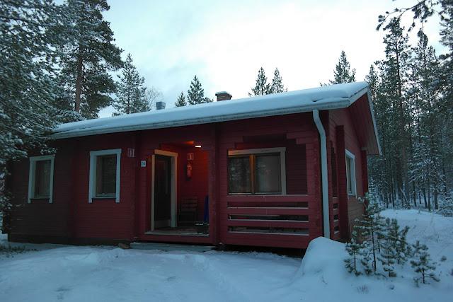 Chalé vermelho de madeira em Ivalo, Finlândia, cercado de neve