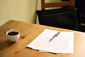foto di un tavolo con foglio e penna sopra