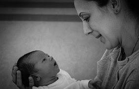 Mutter schaut Neugeborenes an