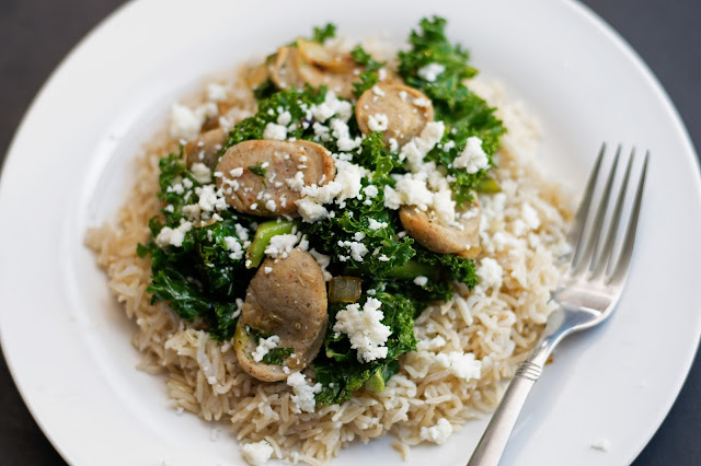 The Chicken Sausage and Kale on a white plate, over rice, with a fork to the side.