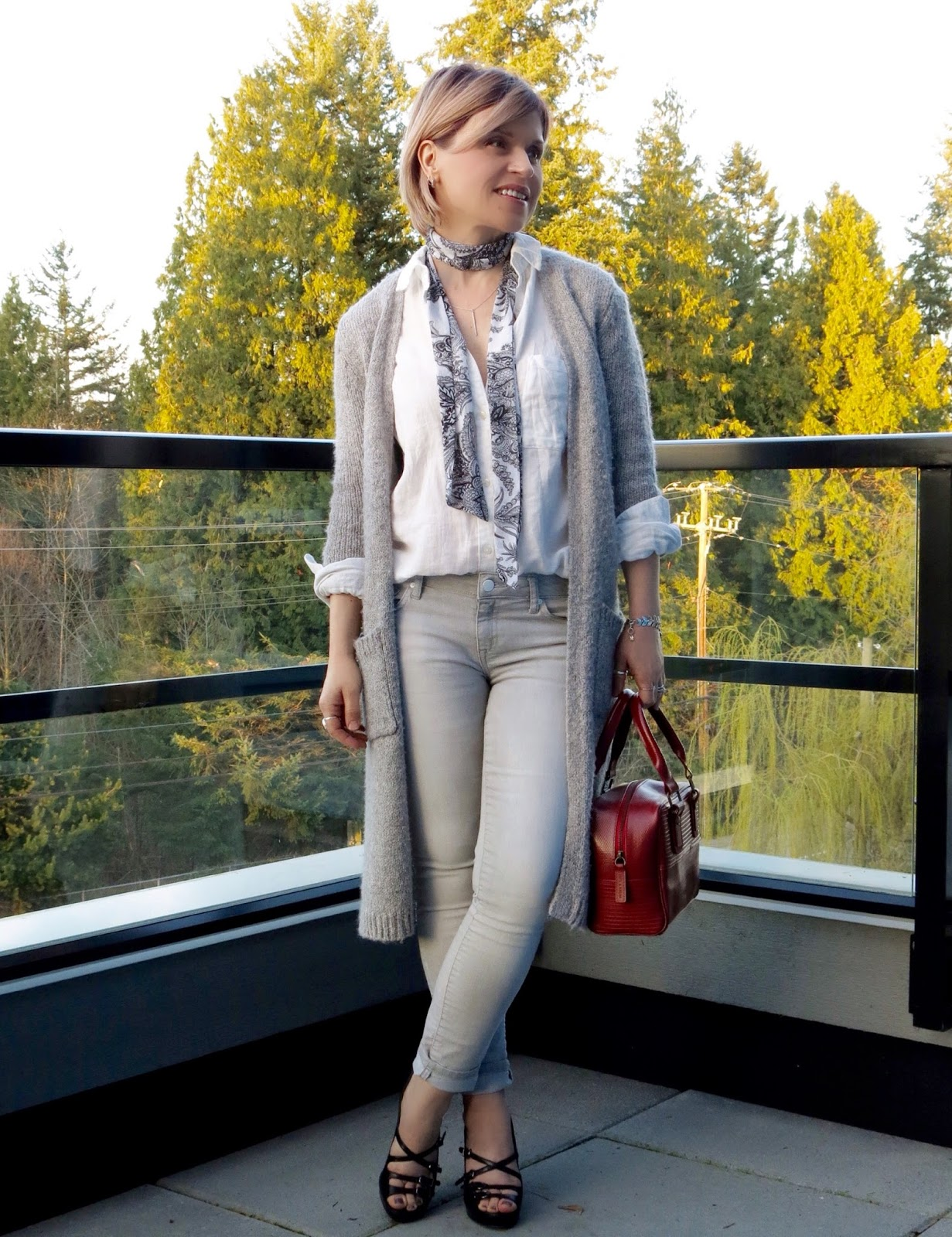 styling a white shirt with a long cardigan, grey skinny jeans and scarf, and strappy heels