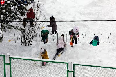 Дети играют в сугробе в детском саду