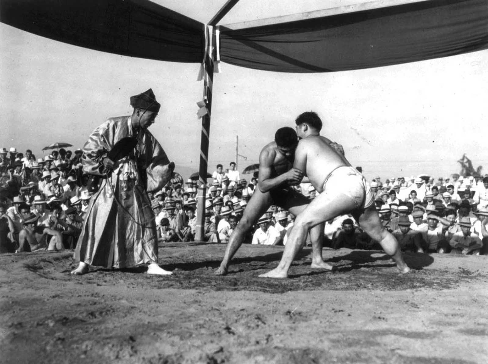 A referee in traditional dress watches over a Sumo wrestling match in front of Japanese-Americans interned at Santa Anita, California.
