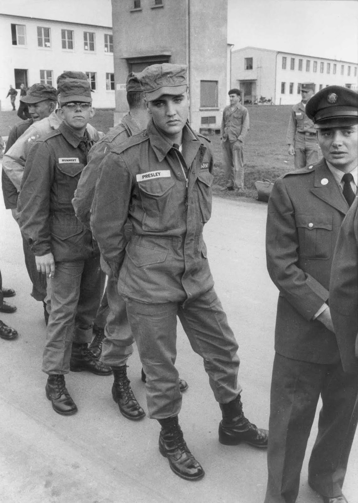 Presley stands in line with other enlisted men and officers on a military base, Germany.