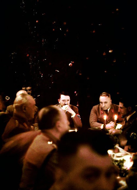 Grasping his knuckles, a pensive Hitler looks down the table at dozens of Nazi soldiers at a Christmas meal in Munich.