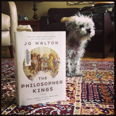 A hardcover copy of The Philosopher Kings stands upright on a red patterned carpet. Its white cover features a rondel filled with Raphael's painting of scholars debating at the School of Athens. Some distance behind the book, Murchie sits with his paws together and his attention focused on something off to the viewer's left.