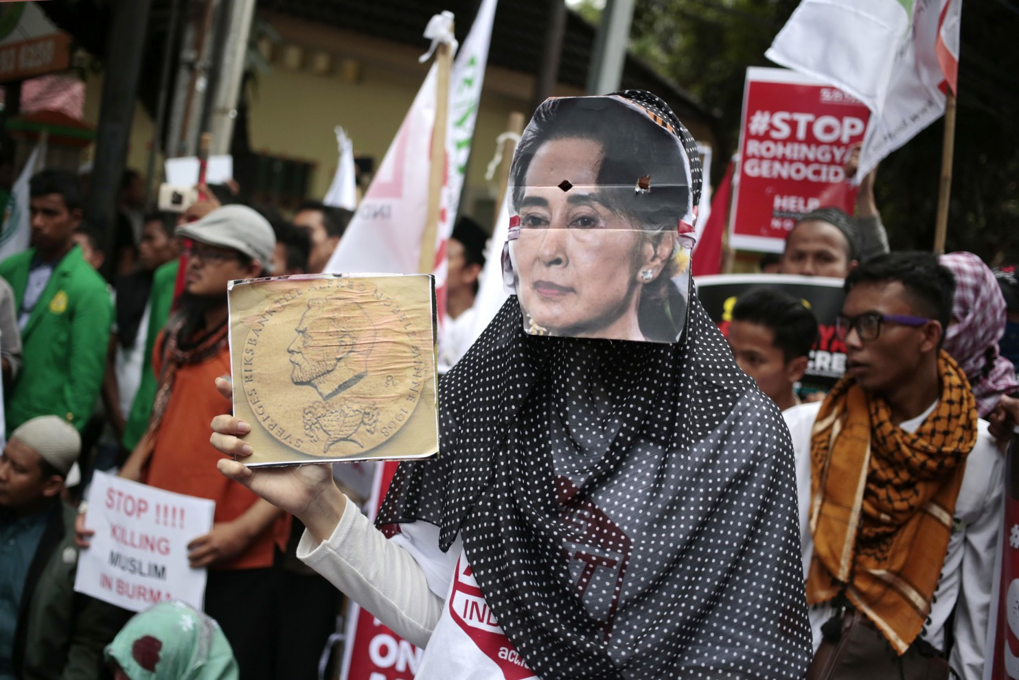 In This Nov 25 2016 File Photo A Muslim Woman Wears A Mask Of Myanmars Foreign Minister Aung San Suu Kyi During A Rally Against The Persecution Of