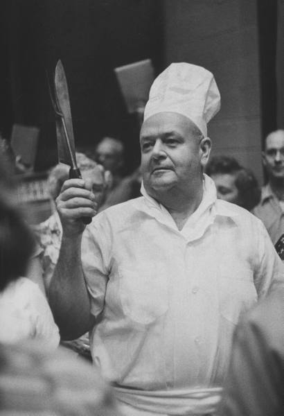 A chef holds the tools of his work during a Labor Day celebration