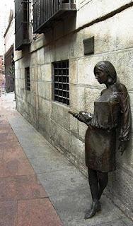 La escultura apoya la espalda en la pared y sostiene con el brazo derecho varios libros.