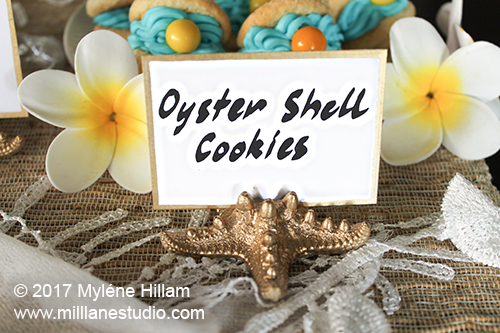 Gold painted resin starfish holding a food label on a tropical buffet.