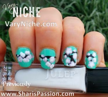 Fingernails with pale pink, white, & mauve flowers dotted over a dark brown branch running across nails with a teal background.