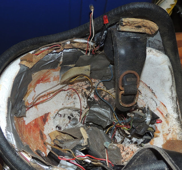 Interior view of battered red helmet showing hideous mess of wires and tape