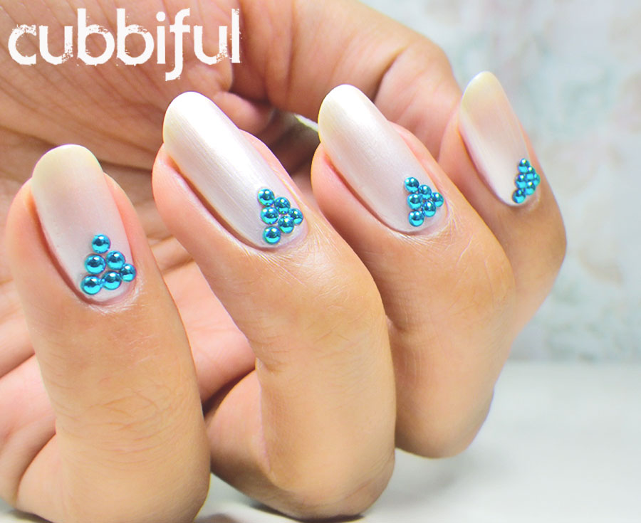 elegant pearly white nails with studs