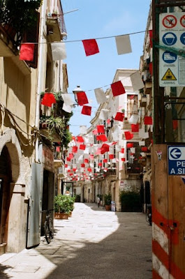 Red and white flags in bari Italy by Frederica Patmore