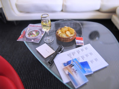 Modern dolls' house miniature Noguchi coffee table holding a glass of champagne, a bowl of chips, a Virgin Australia magazine, a selection of postcards, a pen and a sheet of address labels.