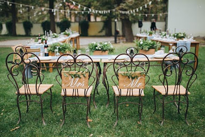 Tables and wrought iron chairs set outdoors for a wedding