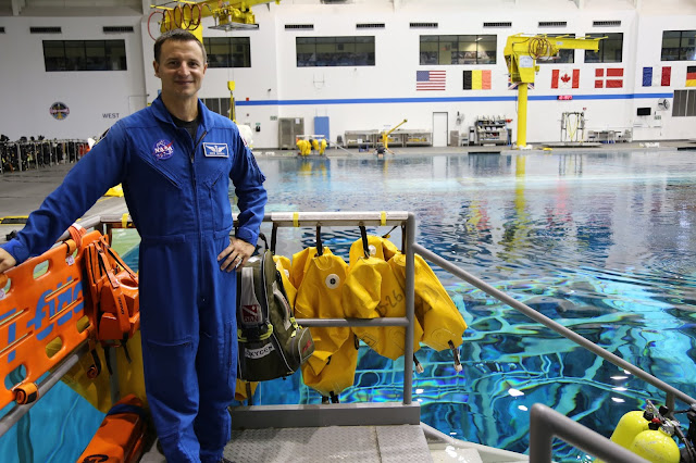 A man in a NASA flight suit stands by a pool