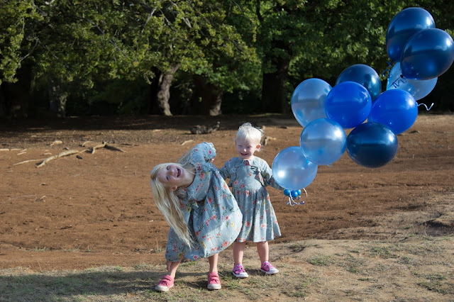 A toddler holding a bunch of balloons next to her sister who is bent over and messing around