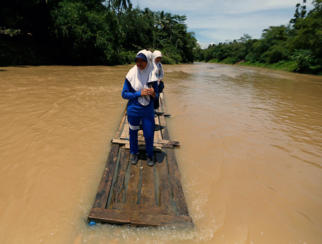 School girls crossing a river on a makeshift raft in Indonesia
