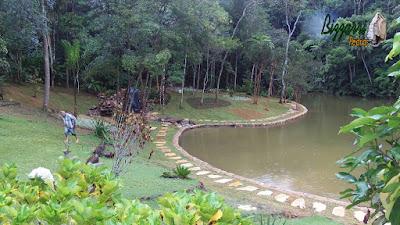 Execução do caminho com pedras em volta do lago com o muro de pedra em volta do lago, sendo caminho com pedra cacão de São Tomé com junta de grama.