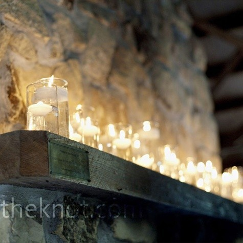 Votive candles resting in water look elegant on this wood mantel.
