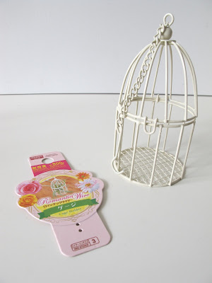 Wire Daiso bird-cage ornament, next to its label.