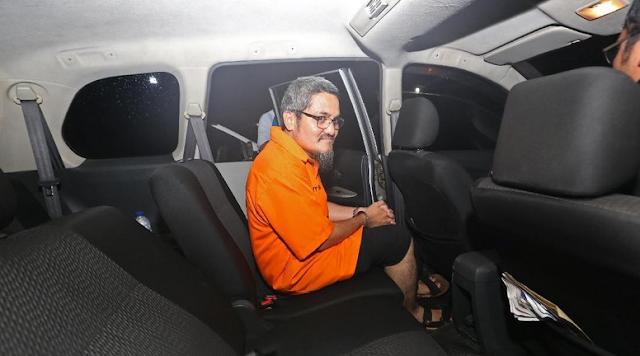 Jonru tampak memakai celana pendek hitam dan sandal. Jonru kemudian dibawa masuk ke mobil (Foto: ANTARA FOTO/Reno Esnir)